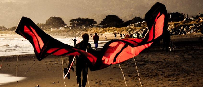 kiteboarder walking up beach